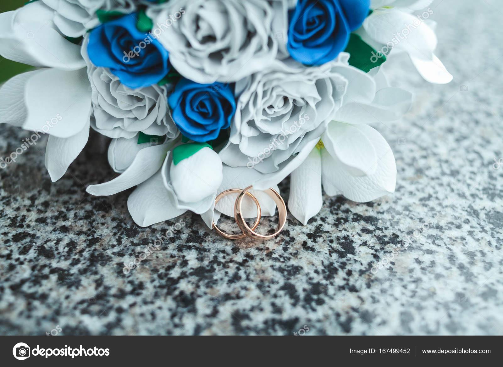 Fedi in oro su una piastrella di marmo con un bouquet della sposa da