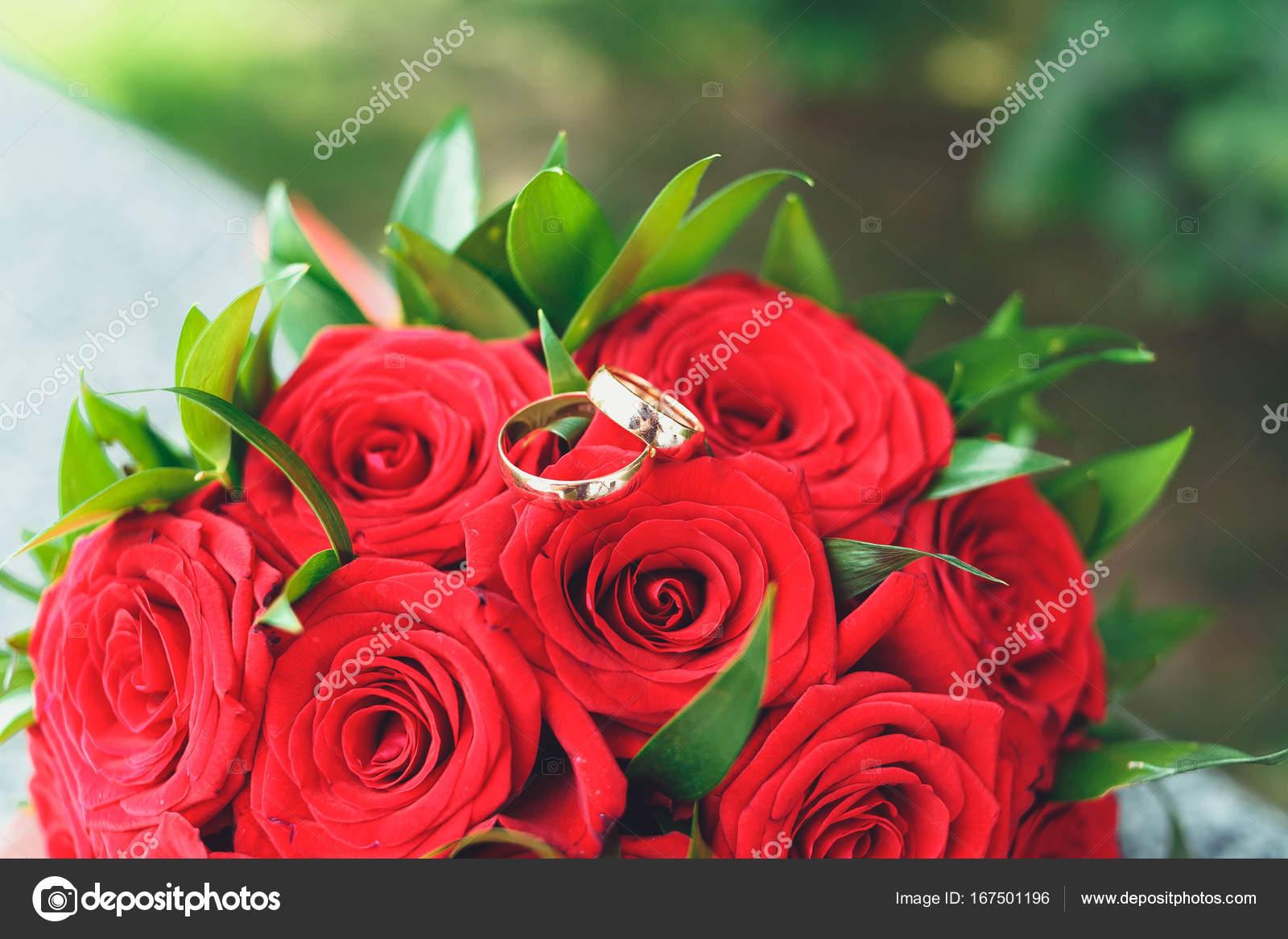 Fedi nuziali dorate su una piastrella di marmo con un bouquet della
