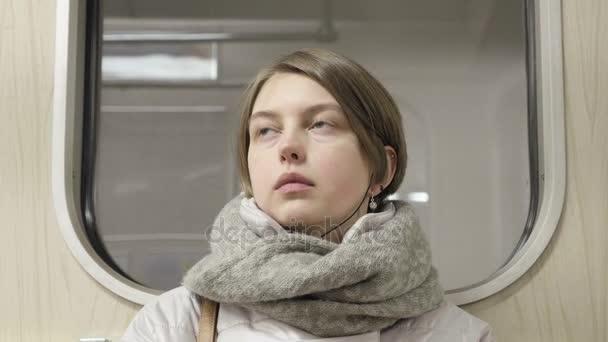 Mladá žena jede vlakem a poslouchat hudbu