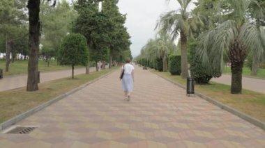 Pretty girl walking in the park of resort. Batumi city, Georgia