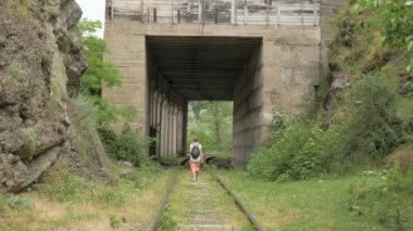 Young girl walks on the reailway in the tunnel
