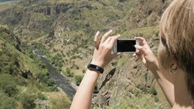 Young woman makes a photo of canyon in mountains - Georgia