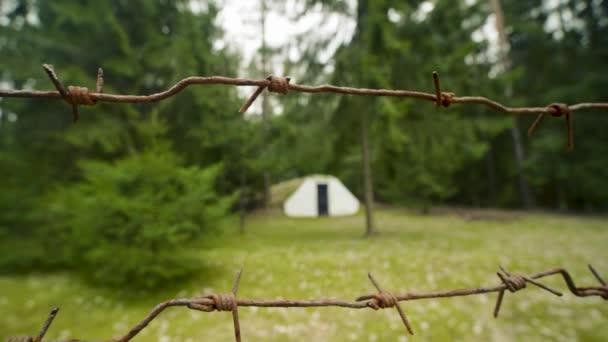 Malý vojenský starý bunkr obklopený ostnatým drátem v letním lese