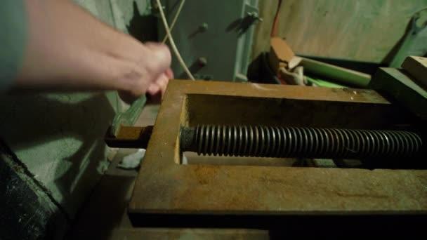 Mann greift in Werkstatt nach Schraube in rostigem Schraubstock, altes Werkzeug verstaubt