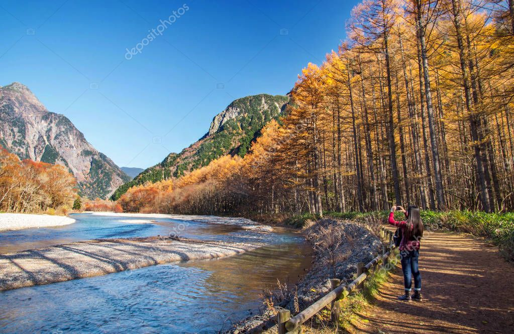 Matsumoto, Nagano, Japan - November 7,2016. A tourist use mobile phone to taking photo of Colorful Autumn Landscape in Kamikochi National Park