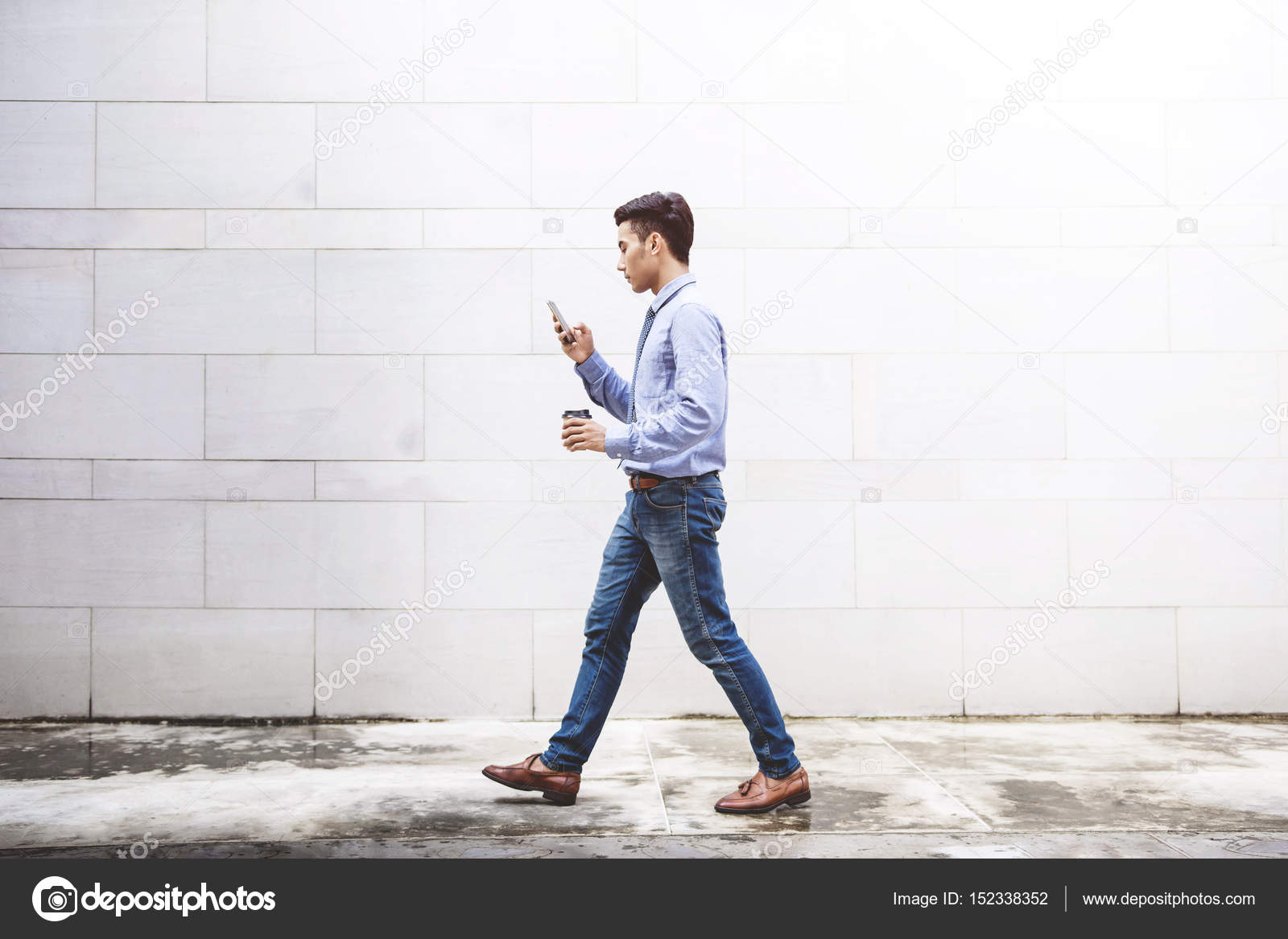 4a71f4b756 Young motivation Businessman use smart phone while walk outdoor building