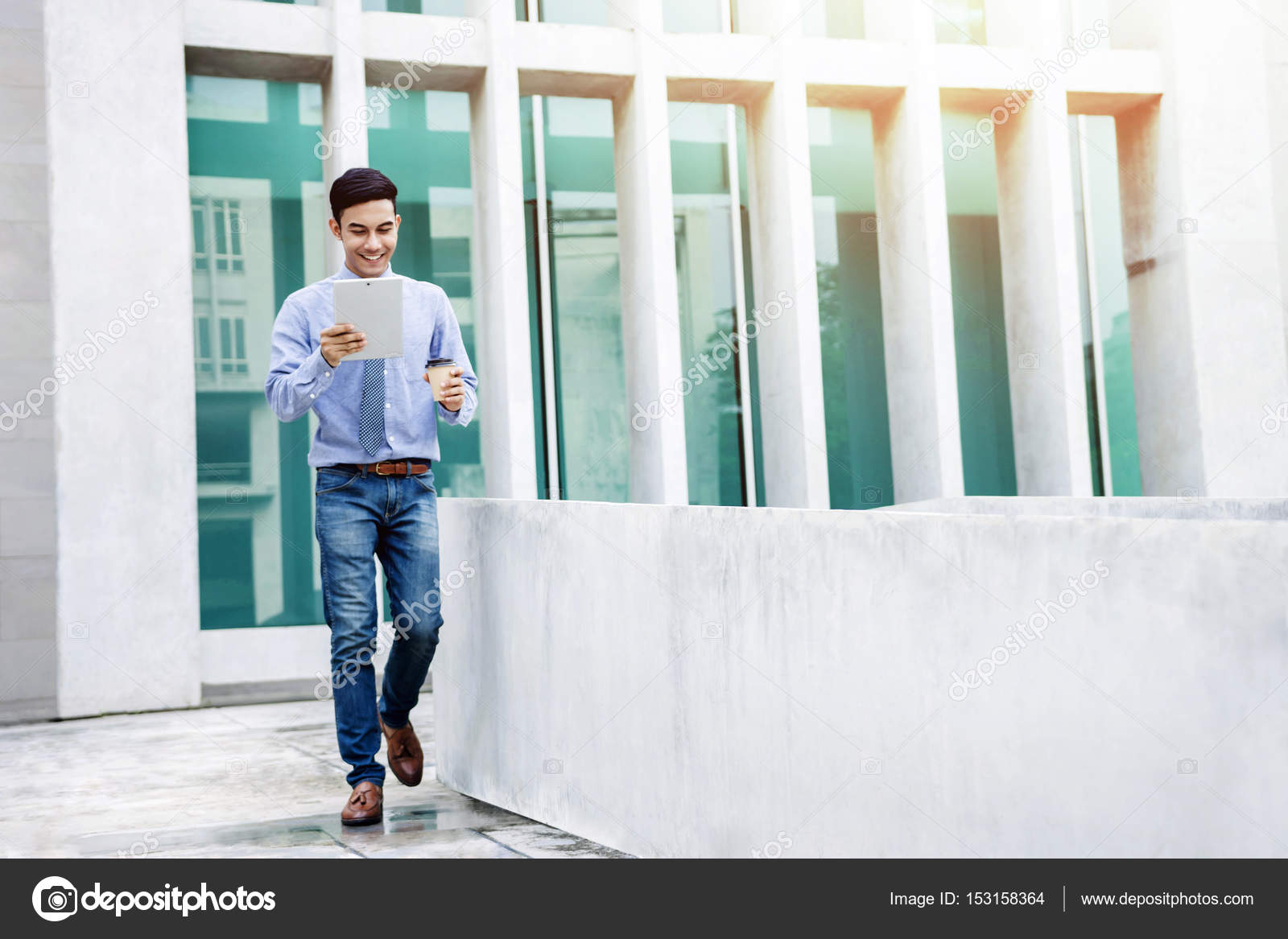 786e27895d Happy Young and modern attractive Businessman in casual wear use a digital  tablet while walk outside office building