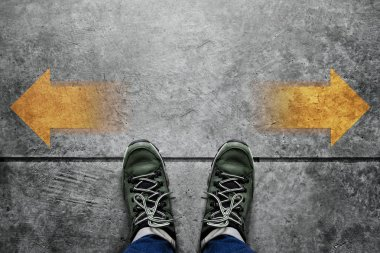 Making Decision Concept, Top view of Male with Casual Adventure shoes with Arrow Left and Right present over Grunge Cement Concrete Crossroad Background