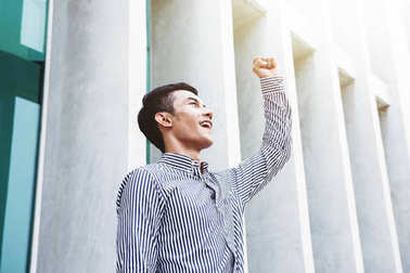Asian Young and Happiness Businessman in Raised arms in Cheerful posture to Celebrate his Life at outside office building, Successful and business achievement concept