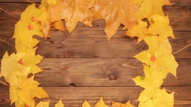 gelbe und orangefarbene Ahornblätter mit roten Äpfeln und Eschen auf dunkelbraunem Holztischhintergrund. rechteckiger Rahmen aus Blättern. Herbst und Herbstkonzept. ein Blatt fällt herunter