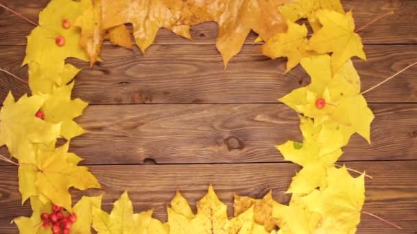 Žluté a oranžové lístky z javorového dřeva s červenými droboučkými jablky a popelůvkou na tmavě hnědém dřevěném stole. Obdélníkový tvarovaný rám z listů. Koncepce pádu a podzimu.