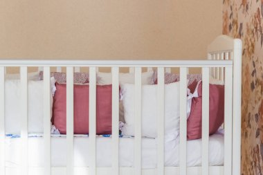 Baby bed with white and Burgundy color pillows with laces. Cot on wheels in the bedroom with pastel yellow colors in the morning. Harsh sun light come from window.Minimalistic interior