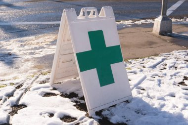 A sign with a green cross on a snowy sidewalk near a newly opened marijuana dispensary in Oregon.