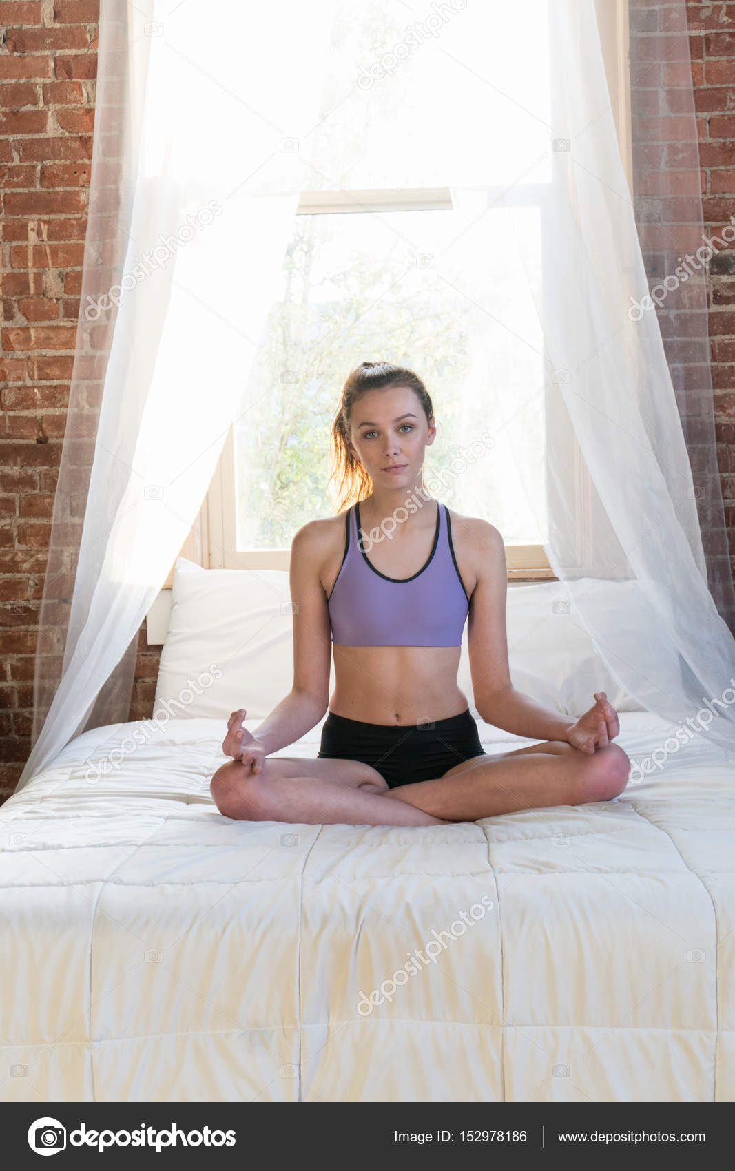 1860dc6707 Young adult woman wearing sports bra and shorts sitting yoga style on bed  on a summer