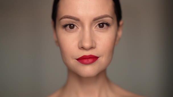 Detailní portrét usměvavé ženy, která se dívá do kamery ve studiu. Mladá atraktivní sebevědomá brunetka dáma se usmívá na bílém pozadí. Ženská přirozená krása. Zpomalené video