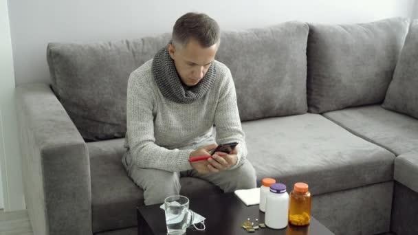 Kranker Mann misst Körpertemperatur und ruft zu Hause den Arzt an