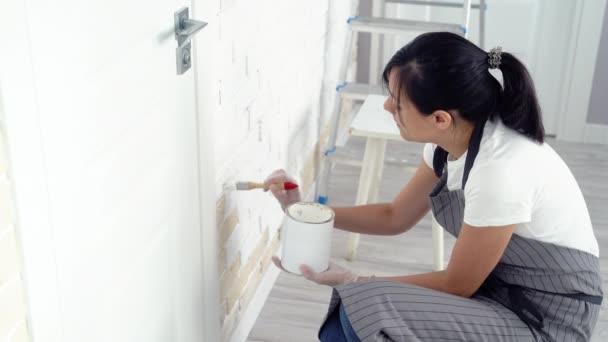 junge Frau beim Bemalen der Wandfarbe in einer Wohnung oder einem Haus.