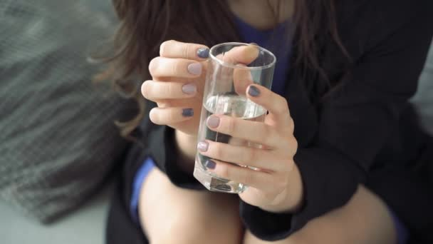 Close-up of a womans hands tapping her fingers on a glass of water. Stress and anxiety.