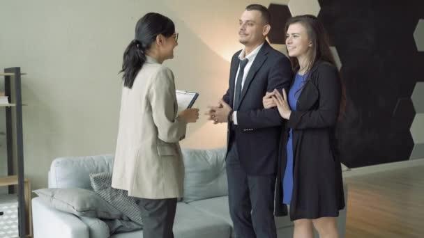 Profesionální realitní agent představuje mladý pár dům nebo byt.