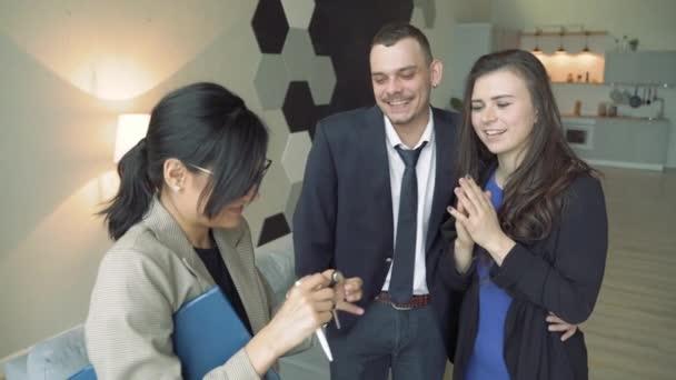 Profesionální realitní agent předává mladý pár klíče od bytu nebo domu.