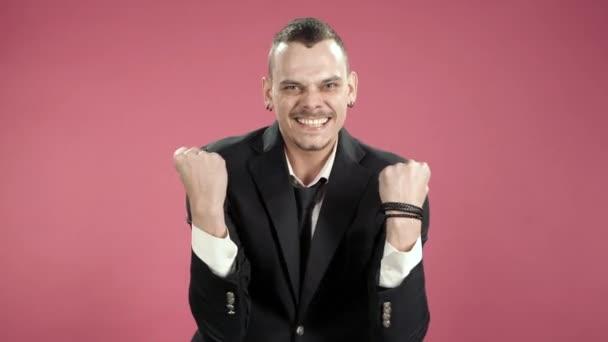 Mladý muž hipster v obleku radostně ukazuje ano gesto na kameře přes růžové pozadí