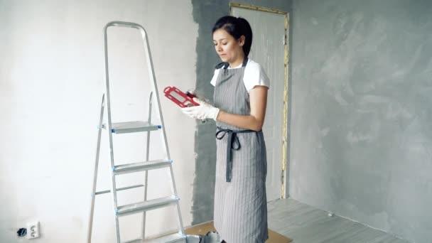 junge Frau in Schürze und Handschuhen bereitet sich auf das Bemalen der Wände vor