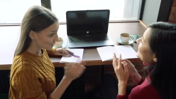 Two young smiling women discussing anything gesticulating with their hands in a cafe or office