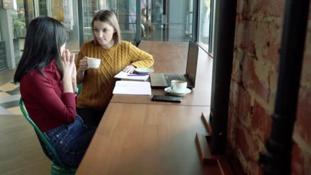 Fiatal nők beszélgetnek és kávéznak egy kávézóban vagy irodában