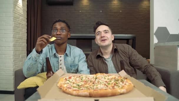 Dva přátelé sledují sportovní zápas v televizi. Chlapi pijou pivo a jedí pizzu a občerstvení, zatímco sedí doma na gauči.