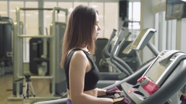Fitness woman doing cardio training walking on treadmill in gym. Athletic girl using run machine in fitness center
