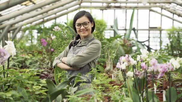 Portrét mladé usměvavé zahradnice nebo květinářky stojící mezi květinami a rostlinami ve skleníku.
