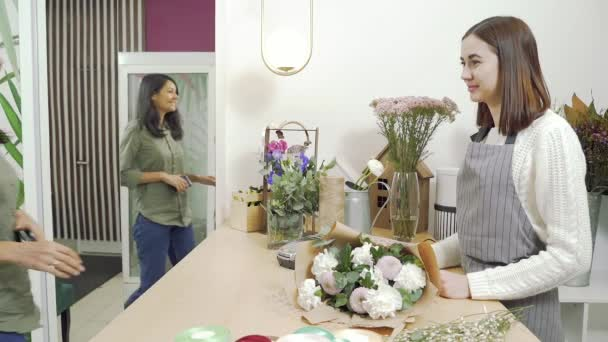 Young brunette woman buying flowers bouquet paying with NFC technology with smart phone credit card in flower shop.