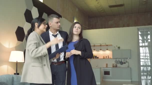 Professional real estate agent presenting young couple a house or apartment. Young couple viewing new property and ready to become homeowners.