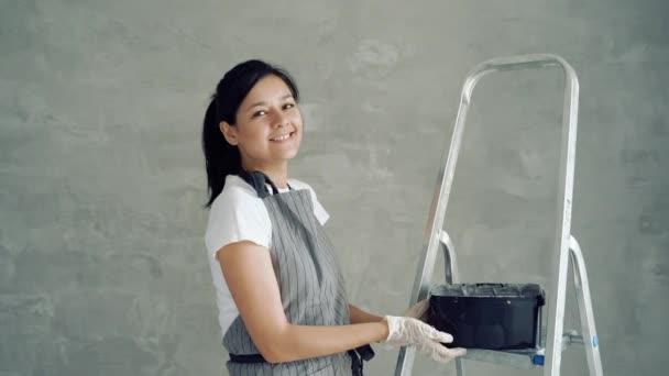 Porträt einer jungen lächelnden Arbeiterin, die ein Glas mit Farbe oder Gips zeigt. Bau, Reparatur und Renovierung