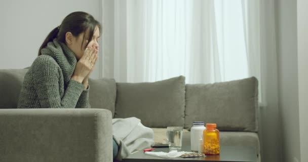 Junge kranke Frau mit Husten und Schnupfen nimmt Tabletten, während sie zu Hause auf dem Sofa sitzt