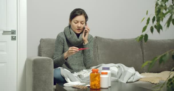 Porträt einer kranken jungen Frau, die die Körpertemperatur misst und zu Hause auf dem Sofa zum Arzt geht.