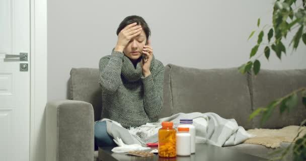 Porträt einer jungen kranken Frau, die mit einem Arzt spricht und während einer Grippe oder Erkältung zu Hause ein Thermometer hält