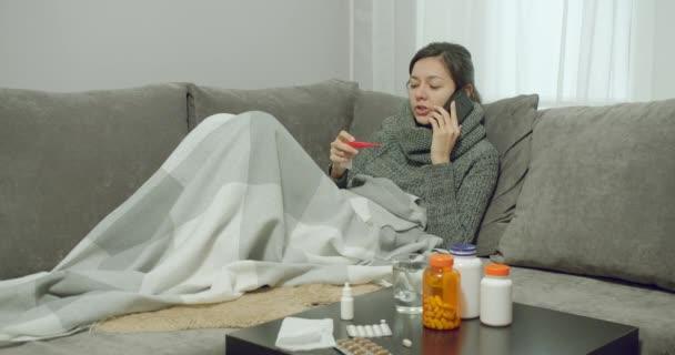 Junge kranke Frau in ein Plaid gehüllt und telefoniert während einer Krankheit mit dem Arzt, während sie zu Hause auf dem Sofa sitzt.