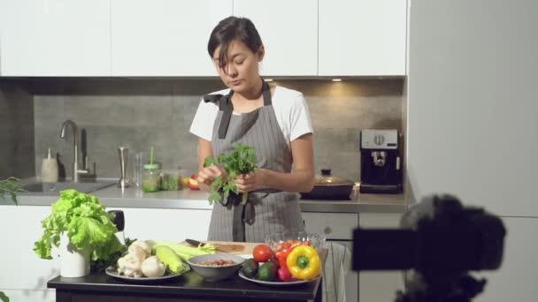 Atraktivní mladá žena nahrává video o zdravém stravování na digitálním fotoaparátu v kuchyni doma. Logování a koncept sociálních médií.
