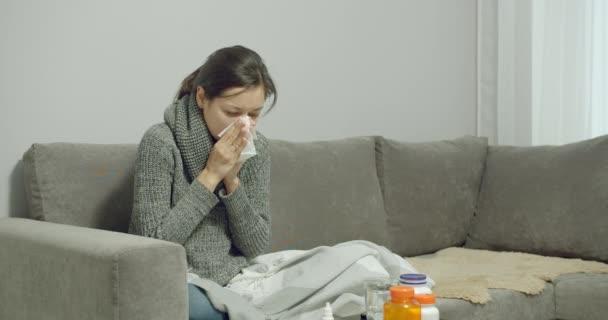 Junge kranke Frau mit Husten und Schnupfen mit Nasenspray, während sie zu Hause auf dem Sofa sitzt. Erkältungen oder Allergien.