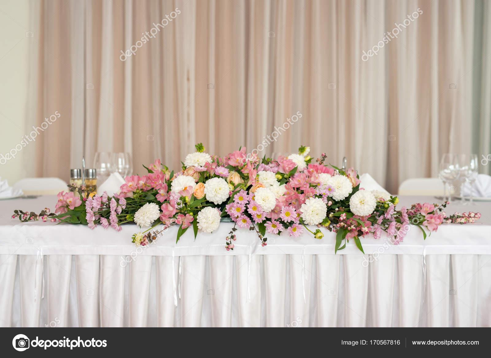 Belle décoration florale sur une table dans un restaurant de mariage.  Nappes blanches, salle lumineuse\u2013 images de stock libres de droits