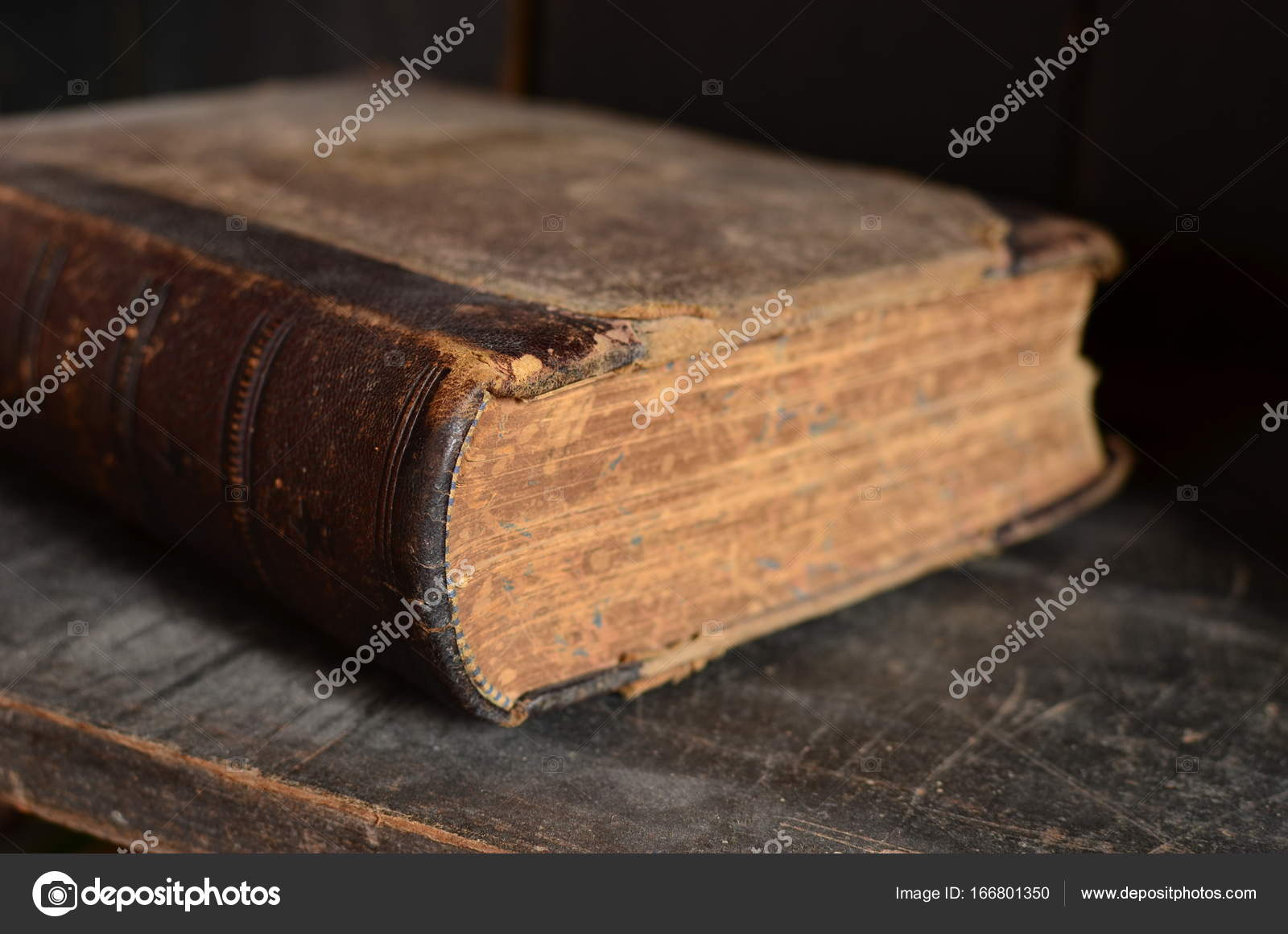 Old Leather Bound Book Laying On A Dusty Wooden Bookshelf Stock Photo