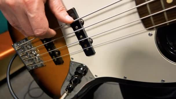 Detailní záběr rukou basák hraje rockovou hudbu s basovou kytaru na koncertě v klubu s krásným světlem