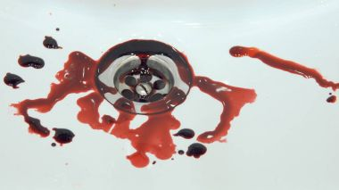 Splashes of blood dripping into the sink in the bathroom