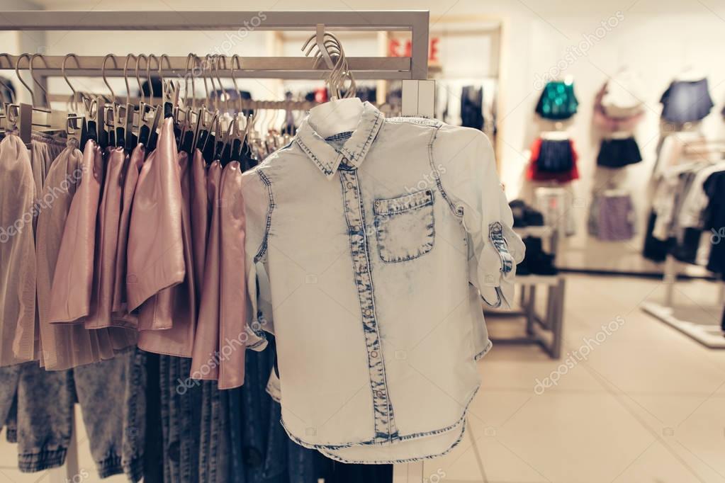 e2018f4c30ea Negozio di abbigliamento. Camicia in negozio di vestiti. Camicia in denim in  centro commerciale — Foto Stock © azovtcev161  145986079