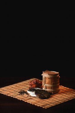 The composition of puer tea with golden toad on a bamboo mat.