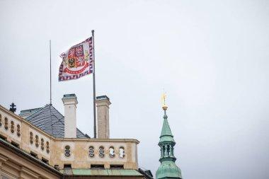 Official flag standard of the president of Czech Republic floating above Prague Castle (Prazsky Hrad) with its slogan in Czech, Pravda Vitezi, meaning justice prevails