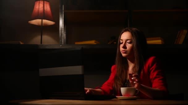 Inspiroval se šálek čerstvé kávy. Promyšlené mladá žena v chytré oblečení drží šálek kávy a koukal s úsměvem, když seděl u svého pracovního místa v kanceláři
