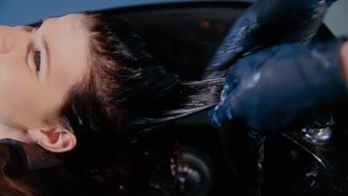 Krásná mladá žena s kadeřnicí mytí hlavy v kadeřnictví