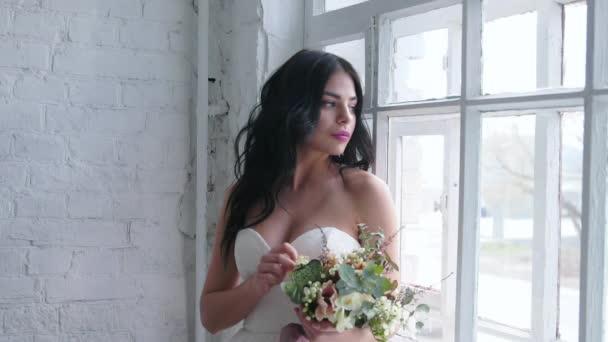 Nevěsta, krásná bruneta postavení v svatební šaty s kytici okna
